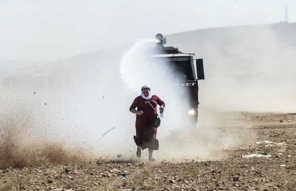 A Kurdish woman runs away from a water cannon during clashes with Turkish soldiers near the Syrian border. © Bülent Kılıç